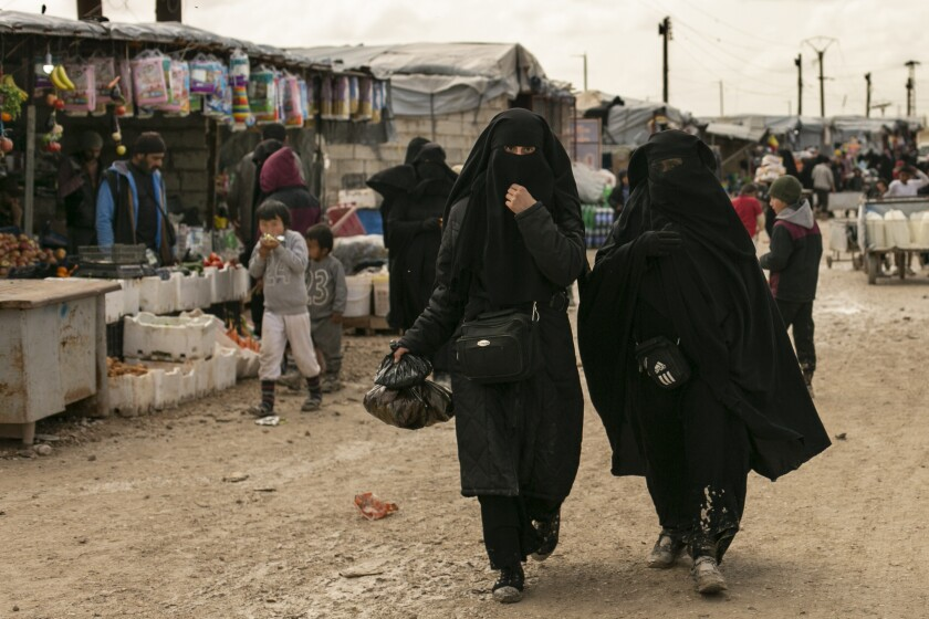 In this March 31, 2019 photo, women shop in the marketplace at Al-Hol camp, home to families of Islamic State fighters, in Hasakeh province, Syria. The Islamic State group could get a new injection of life if conflict erupts between the Kurds and Turkey in northeast Syria as the U.S. pulls its troops back from the area. The White House has said Turkey will take over responsibility for the thousands of IS fighters captured during the long campaign that defeated the militants in Syria. But it's not clear how that could happen. (AP Photo/Maya Alleruzzo)