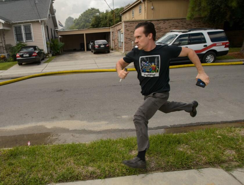 El escritor y actor Gideon Hodge corre hacia su casa en llamas en Nueva Orleans. Hodge se apresuró a llegar a la estructura y rebasó a los bomberos, los que les gritó que se detuvieran, para poder recuperar su laptop, en la que asegura tenía dos novelas completas. (Matthew Hinton/The Advocate via AP)