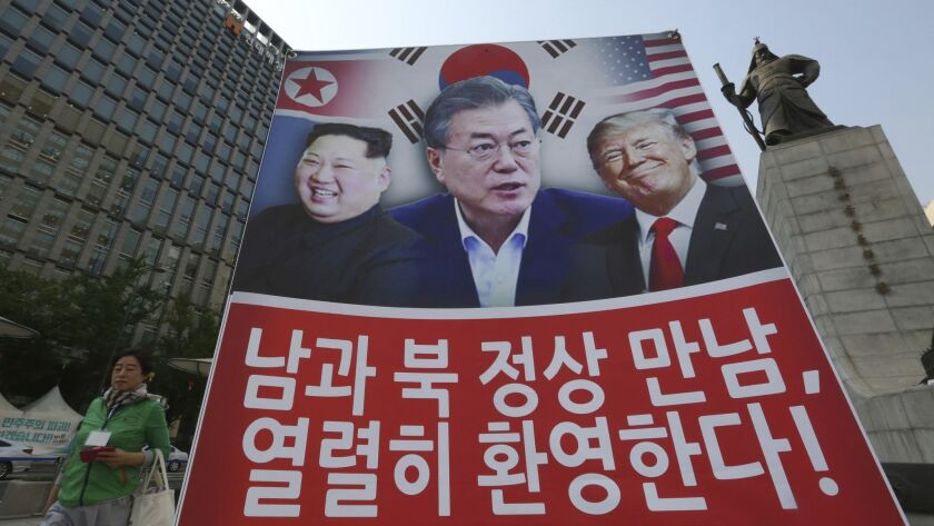 A banner showing North Korean leader Kim Jong Un, left, South Korean President Moon Jae-in and President Trump erected in Seoul to support the summit between the two Koreas on April 27.
