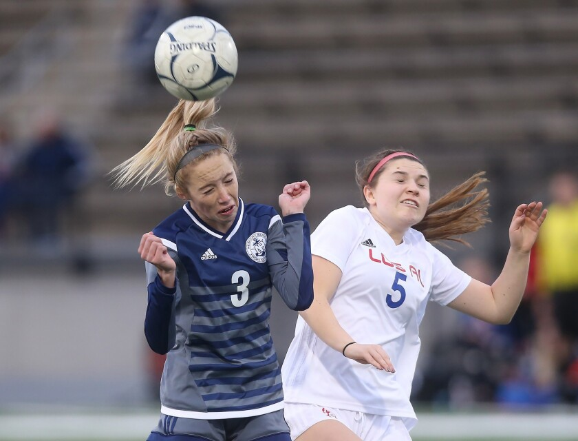 Newport Harbor's Reese Bodas (3) heads the ball as she is bumped by Los Alamitos' Analisa Gjonovich
