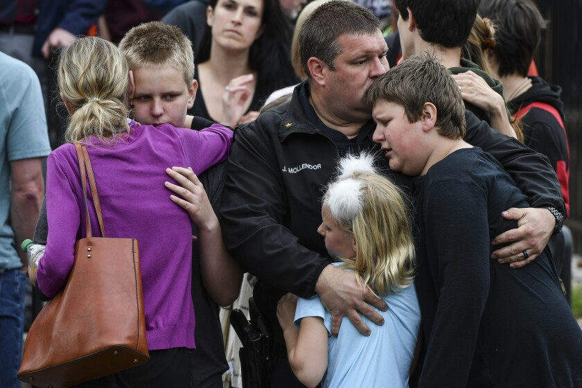 A police officer hugs his kids after they were evacuated to the Recreation Center at Northridge after a shooting at STEM School Highlands Ranch on May 7, 2019, in Highlands Ranch, Colo.