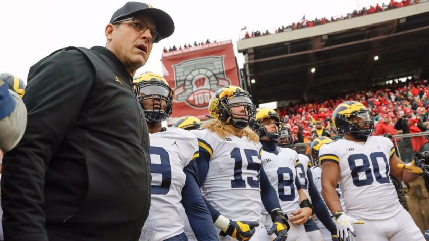 Michigan head coach Jim Harbaugh leads his team to the field before an NCAA college football game ag