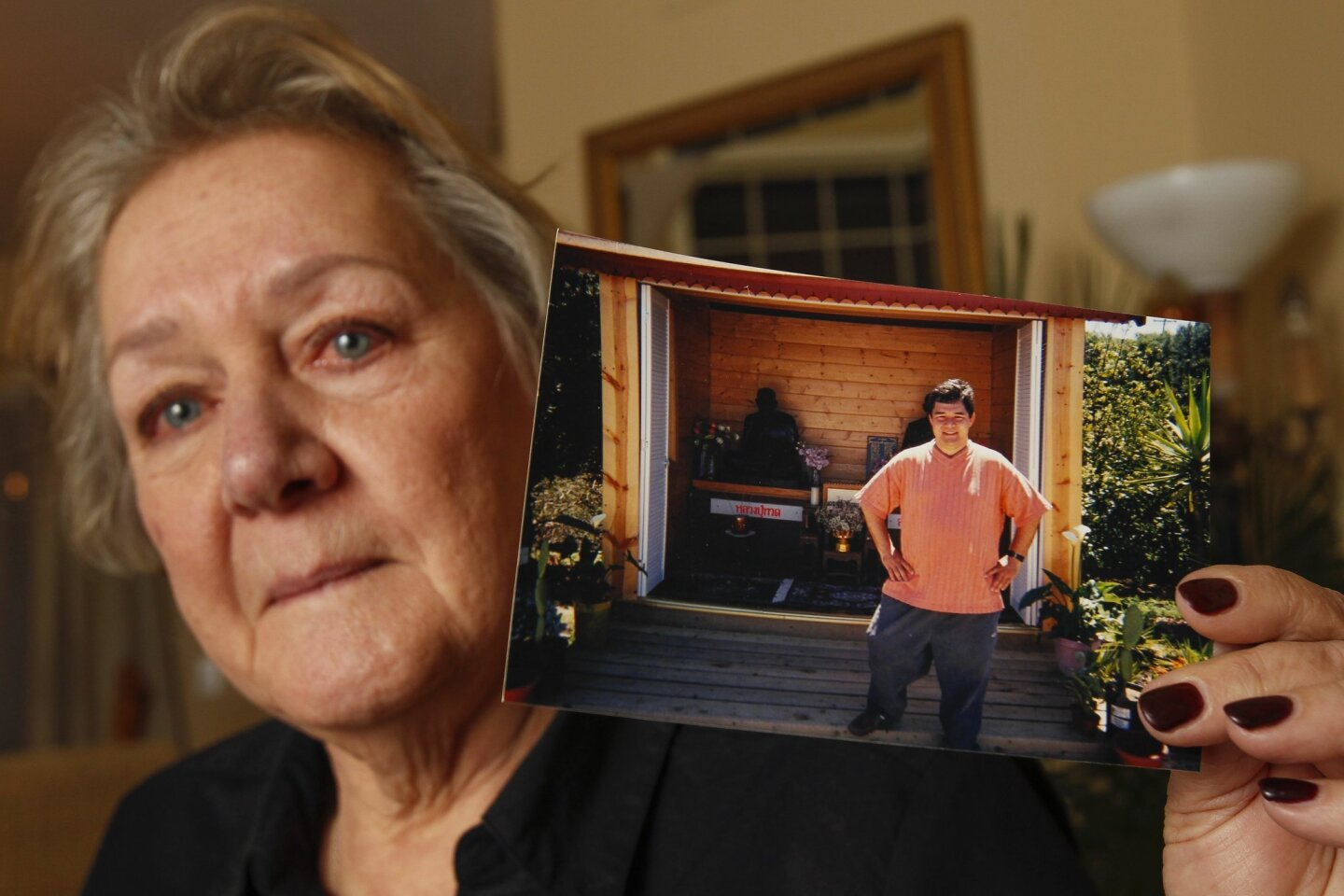 Rochelle Nishimoto, whose son Jason Nishimoto committed suicide in jail after he was arrested by police last September, holds a picture of Jason at the Thai Buddhist monastery in North County that he would regularly go to, while in her home in Vista on Tuesday.
