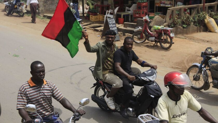 In this 2012 photo, Igbo men carry a Biafra flag during a protest in Nnewi, Nigeria.