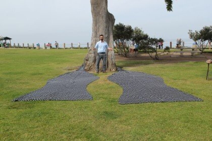 Zach 'ZB' Barnhorst stands in Scripps Park with 120 yards of fabric he hopes will be recognized as the world's largest, self-tie bow tie. He and his crew will tie it Sunday for recordation by Guinness World Records.