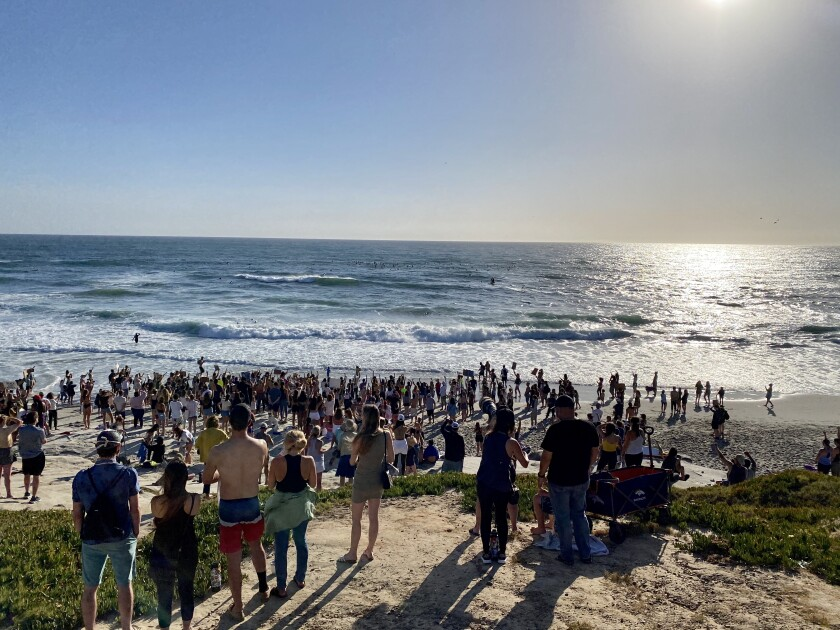 Surfers paddle out at Windansea while others stay ashore to support the Black Lives Matter movement.