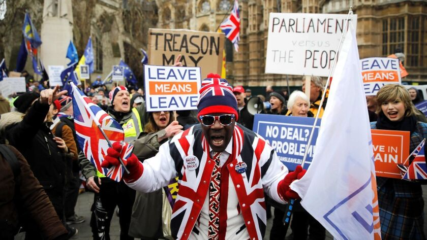 A pro-Brexit activist dressed in Union flag-themed clothes and sunglasses demonstrates opposite the Houses of Parliament in London on Tuesday.