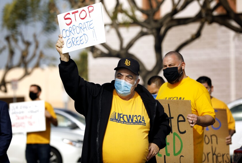 "Howard Simmons, wearing a yellow union shirt, carries a sign that says ""Stop corporate greed!"""