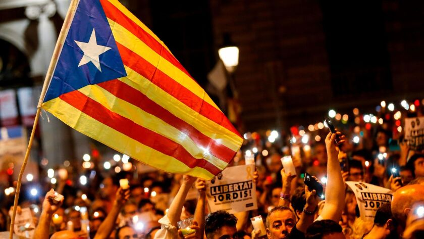 People hold candles and display a Catalan flag during a rally on Oct. 17 in Barcelona, Spain, to protest the arrest of two separatist leaders.