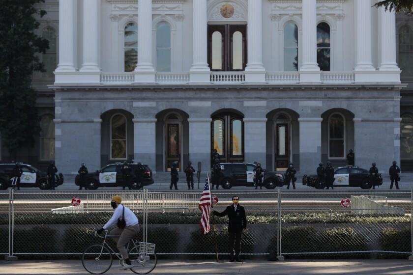 UCR masters student Christian Alvarado, 25, of Sacramento stands with an American flag.