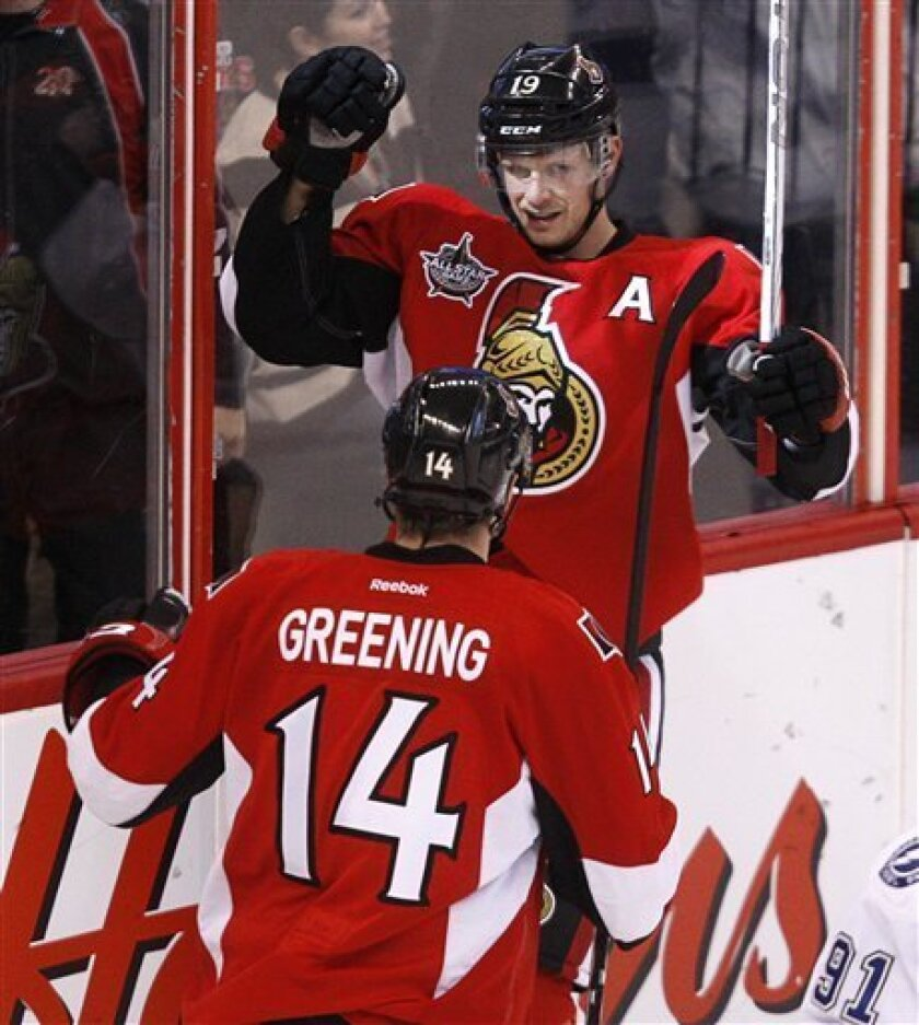 Ottawa Senators center Jason Spezza, rear, is congratulated by teammate Colin Greening (14) after scoring against Tampa Bay Lightning goalie Dwayne Roloson during the second period of an NHL hockey game in Ottawa, Ontario, on Thursday, Jan. 5, 2012. (AP Photo/The Canadian Press, Adrian Wyld)
