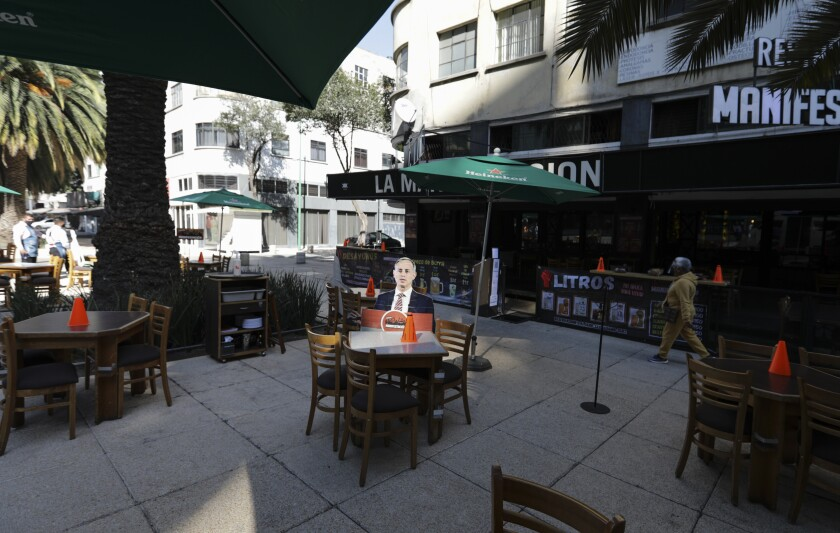 A life-size cutout of Mexican official Hugo Lopez-Gatell at an empty restaurant table outdoors