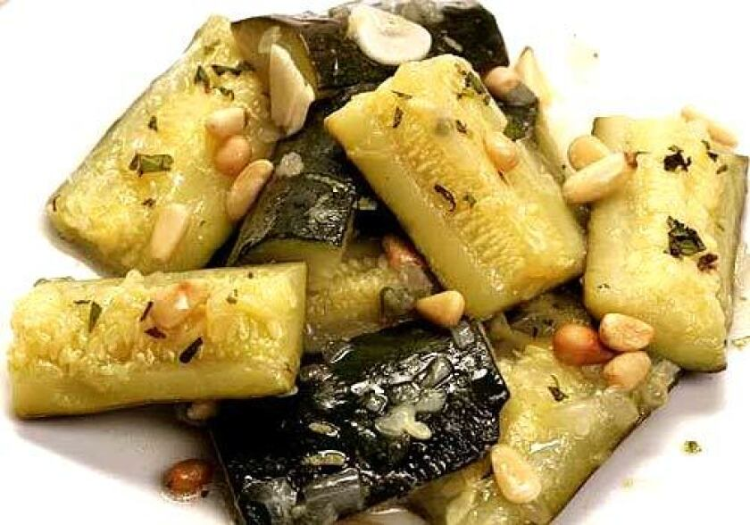 Zucchini with pine nuts are cooked to the texture of butter, tart with lemon and perfumed with fresh herbs.