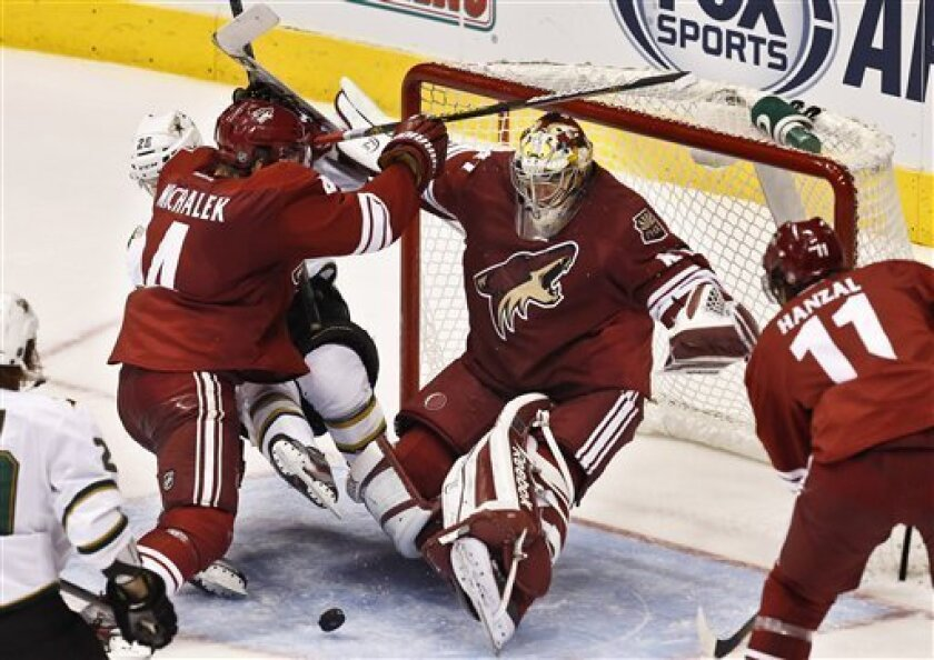 Phoenix Coyotes' Mike Smith makes a save on a shot as teammates Zbynek Michalek (4), of the Czech Republic, and Martin Hanzal (11), of the Czech Republic, defend against Dallas Stars' Matt Fraser (25) in the second period during an NHL hockey game on Saturday, March 9, 2013, in Glendale, Ariz.(AP P