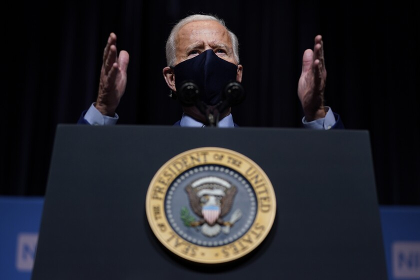 President Biden gestures while speaking at a lectern