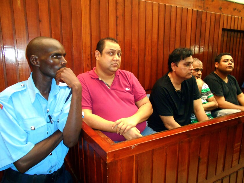 """Baktash Akasha Abdalla (in red shirt) appears in Mombasa Law Courts in Kenya on Feb. 9, 2015, for a bond hearing, along with co-defendants (from third left) Vijaygiri """"Vicky"""" Anandgiri, Gulam Hussein, and brother Ibrahim Akasha Abdalla. The four were arrested in November 2014 after the U.S. issued an Interpol """"red notice"""" for their capture and request for extradition."""