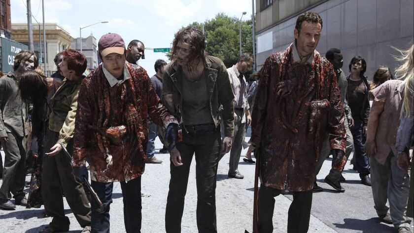 Glenn (Steven Yeun), Zombie and Rick Grimes (Andrew Lincoln) pretend to be zombies in episode 102 of