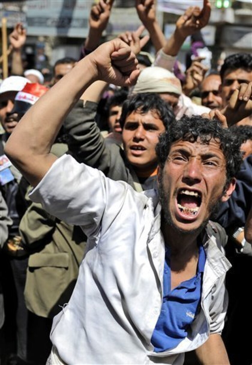 An anti-government protestor shouts slogans during a demonstration demanding the resignation of Yemeni President Ali Abdullah Saleh, in Sanaa,Yemen, Monday, March 21, 2011. Three Yemeni army commanders, including a top general, defected Monday to the opposition calling for an end to President Ali Abdullah Saleh's rule, as army tanks and armored vehicles deployed in support of thousands protesting in the capital. With the defection, it appeared Saleh's support was eroding from every power base in the nation - his own tribe called on him to step down, he fired his entire Cabinet ahead of what one government official said was a planned mass resignation, and his ambassador to the U.N. and human rights minister quit. (AP Photo/Hani Mohammed)