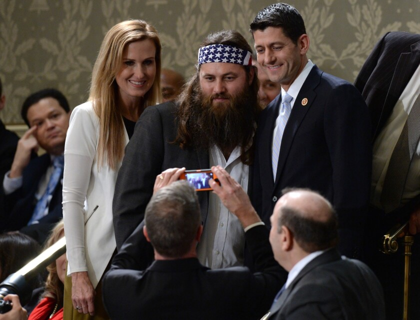 """Korie and Willie Robertson of the television show """"Duck Dynasty"""" pose for a picture with Rep. Paul D. Ryan (R-Wis.) before the State of the Union address."""