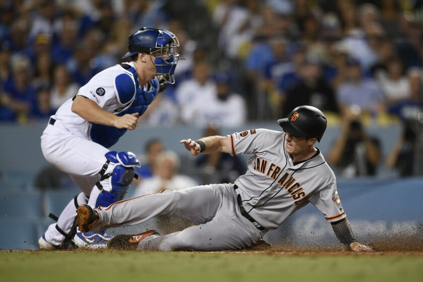 San Francisco Giants' Mike Yastrzemski, right, slides into home in front of Dodgers catcher Will Smith during the fifth inning of Friday's game.