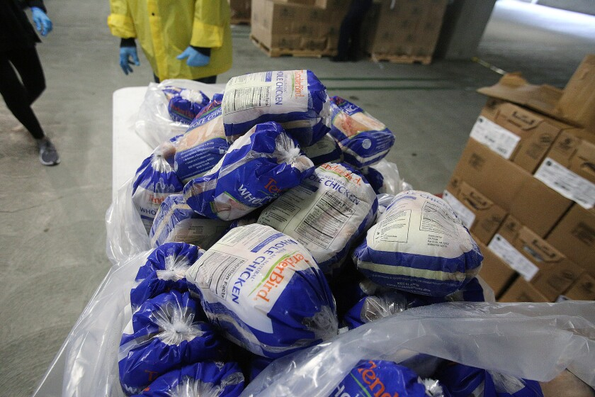 A table with frozen chicken that will be given to people at the drive-through station of the food pantry at Glendale Community College on Tuesday, April 7, 2020.