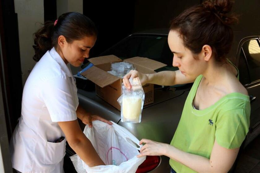 A woman who is part of a Paraguayan network of over 240 young mothers hands over containers of breast milk to a nurse on Feb. 7, 2019 - the network as a whole feeds close to 1,000 babies who cannot be nursed by their own mothers. EFE-EPA/Andres Cristaldo