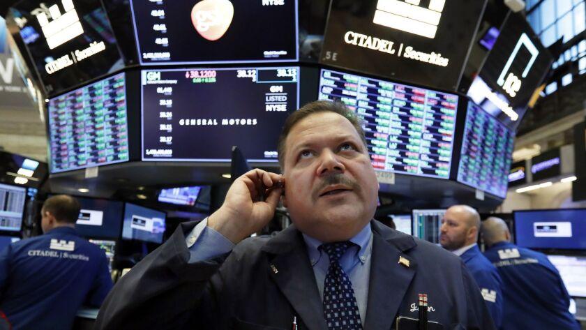 Trader John Santiago works on the floor of the New York Stock Exchange on Monday.