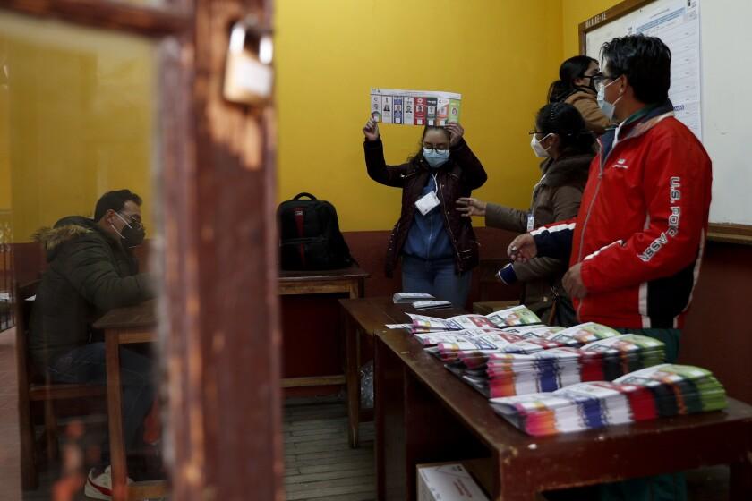 Electoral officials count ballots after polls closed for presidential elections in La Paz, Bolivia, Sunday, Oct. 18, 2020. (AP Photo/Juan Karita)