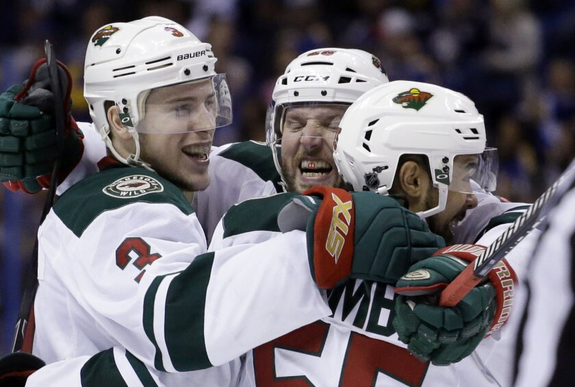 Minnesota Wild's Charlie Coyle, left, is congratulated by teammates Thomas Vanek, of Austria, and Matt Dumba, right, after scoring during the third period in Game 5 of an NHL hockey first-round playoff series against the St. Louis Blues, Friday, April 24, 2015, in St. Louis. The Wild won 4-1. (AP P
