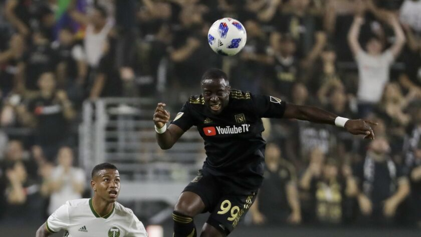 Los Angeles FC forward Adama Diomande, right, heads the ball away from Portland Timbers forward Jere