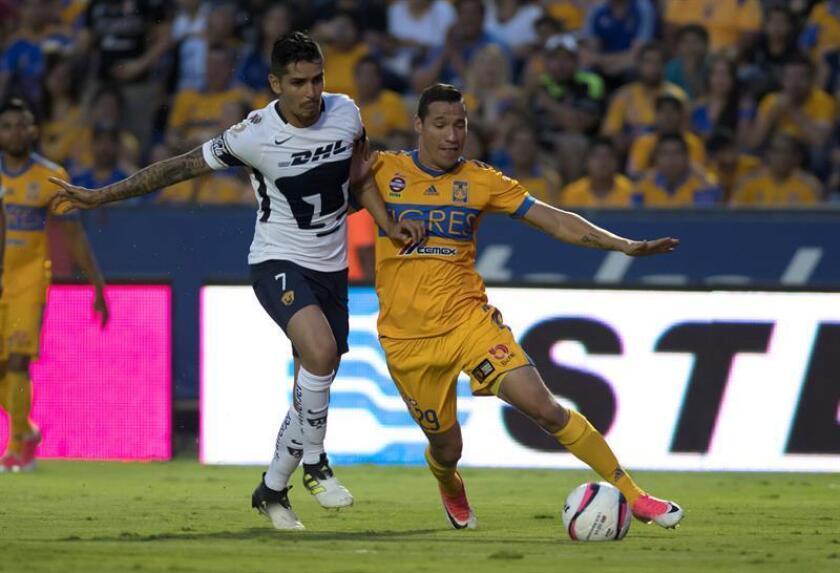 Jesus Dueñas (d) de Tigres disputa el balón con David Cabrera (i) de Pumas de la UNAM. EFE/Archivo