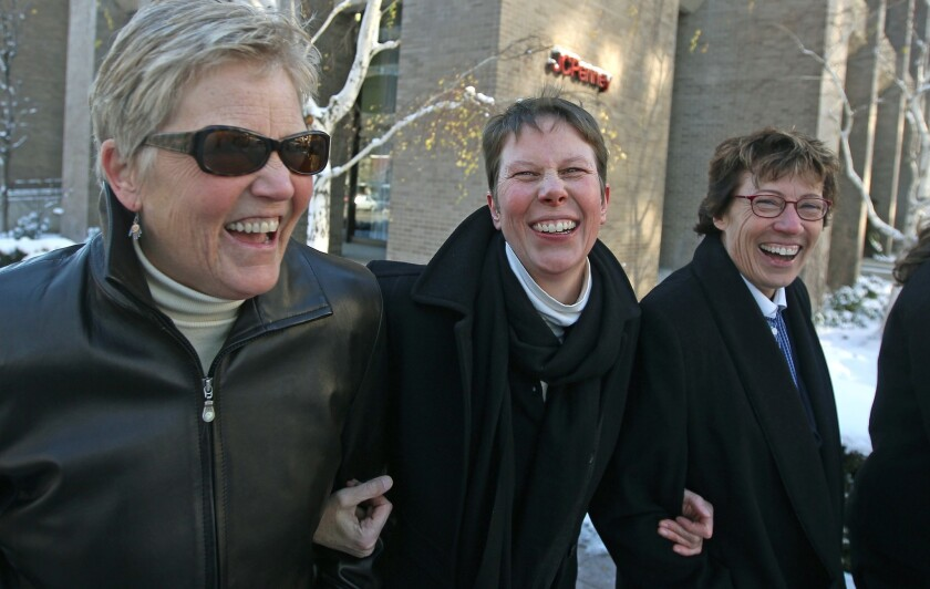 Plaintiff's Laurie Wood, left, and her partner, Kody Partridge, center, walk with their attorney Peggy Tomsic after leaving the Frank E. Moss U.S. Courthouse on Wednesday. A challenge to Utah's same-sex marriage ban by three gay couples was heard this week. A federal judge has struck down Utah's same-sex marriage ban Friday, saying it is unconstitutional.