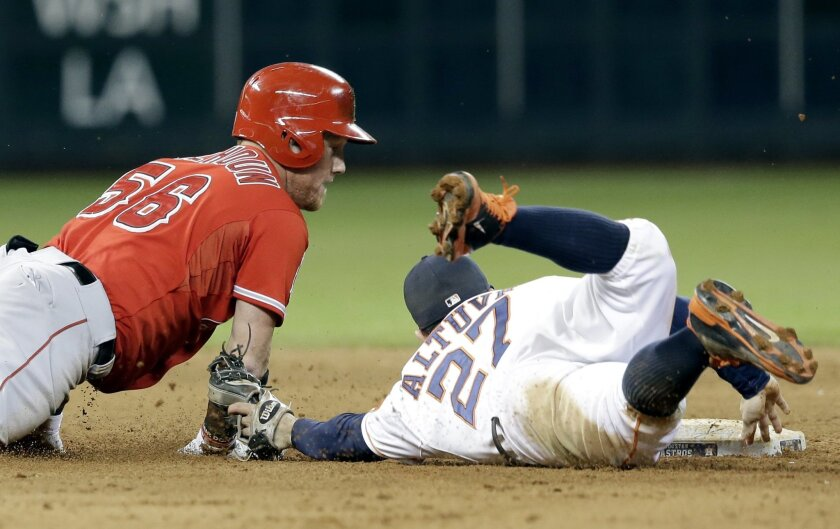 Houston Astros second baseman Jose Altuve (27) keeps his fingers on second base as he tags Los Angeles Angels' Kole Calhoun (56) out in the sixth inning of a baseball game Tuesday, Sept. 2, 2014, in Houston. Calhoun was trying to stretch a single on a line drive to center field. (AP Photo/Pat Sullivan)