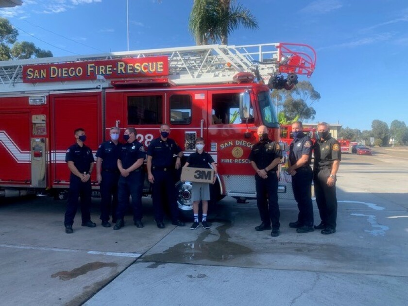 Bishop's School eighth-grader Ezra Granet stands with firefighters after donating 10,000 masks to San Diego Fire-Rescue.