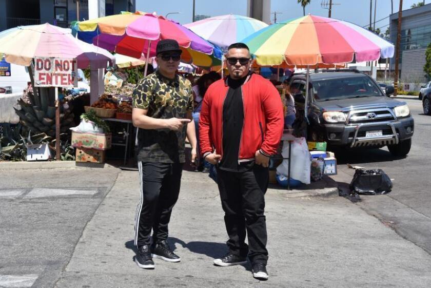 Fotografía de archivo del 14 de abril de 2018 donde aparecen los integrantes del dúo de hip-hop salvadoreño Crooked Stilo, Víctor López (i) y su hermano Johnny López (d), mientras posan junto a productos salvadoreños en la calle de ventas de alimentos de El Salvador, en Los Ángeles, California (EE.UU.). EFE/Iván Mejía