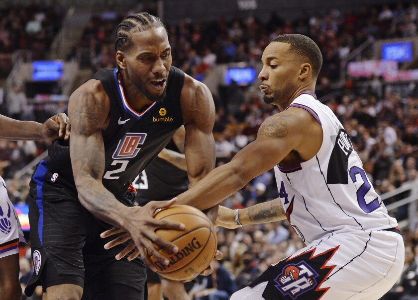 Los Angeles Clippers forward Kawhi Leonard, left, and Toronto Raptors guard Norman Powell (24) battle during the second half of an NBA basketball game, Wednesday, Dec. 11, 2019, in Toronto. (Nathan Denette/The Canadian Press via AP)