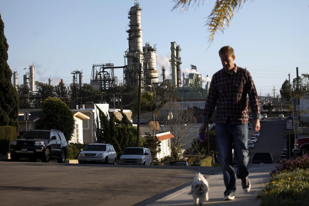 A man walks a dog with an oil refinery in the background