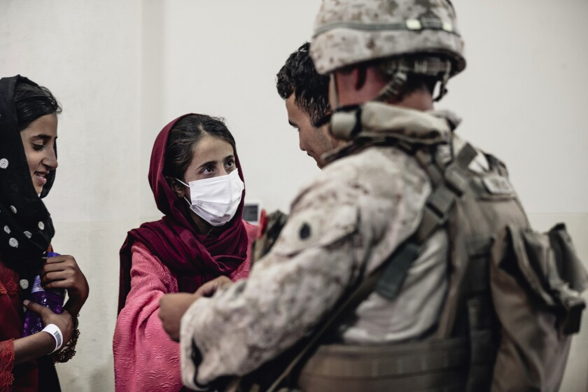 In this image provided by the U.S. Marine Corps, a Marine processes youth to be evacuated.