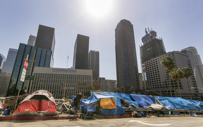 Tents used by the homeless line a downtown Los Angeles street with the skyline behind then in this file photo.
