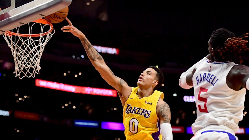 Lakers forward Kyle Kuzma is fouled by Clippers forward Montrezl Harrell during the season opener.
