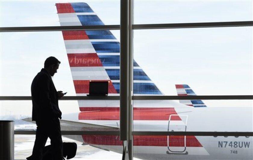 ARCHIVO - En esta fotografía de archivo del 25 de enero de 2016, un pasajero habla por teléfono mientrsa un avión de American Airlines permanece estacionado en el Aeropuerto Nacional Ronald Reagan de Washington. (AP foto/Susan Walsh, archivo)