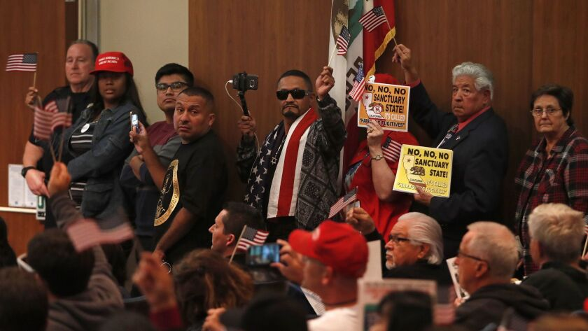 """Opponents of California's Senate Bill 54 hold signs while lining up to speak during Tuesday night's Costa Mesa City Council meeting on whether the city should take an official stand against the """"sanctuary state"""" law."""
