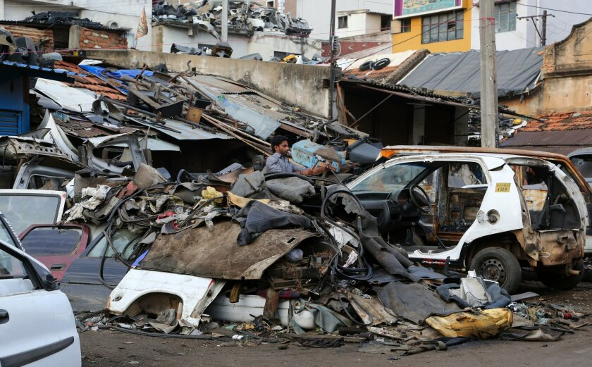 FILE - In this file photo dated Thursday, April 23, 2015, an Indian worker dismantles an old car amid heaps of scrap in Bangalore, India. Climate change could push more than 100 million people into extreme poverty by 2030 by disrupting agriculture and fueling the spread of malaria and other disease