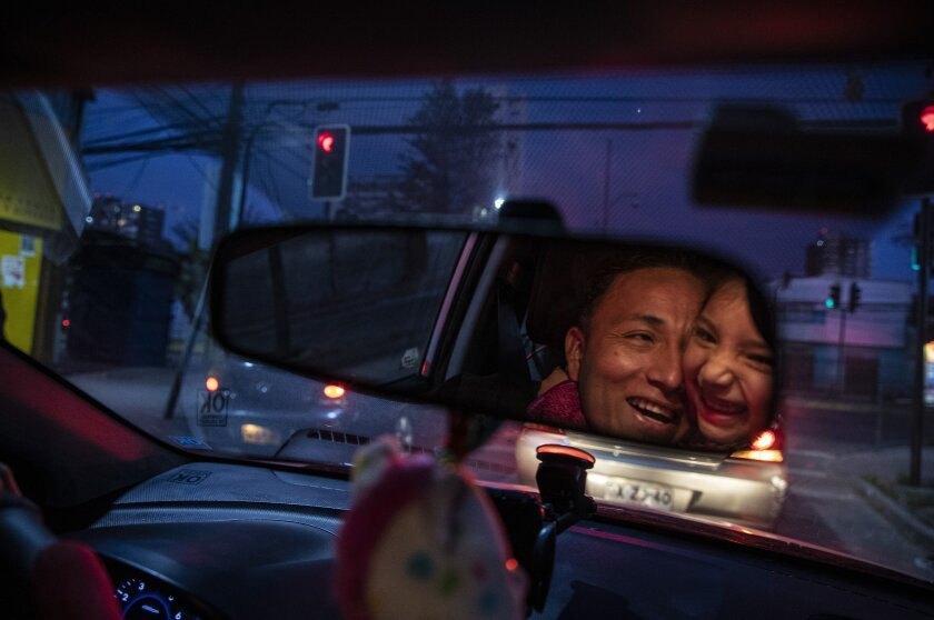 Reflected in the rearview mirror, Jose Collantes gets a hug from daughter Kehity while they're stopped at a red light, as Jose drives his five-year-old home from a playdate in Santiago, Chile, Sunday, Sept. 6, 2020, three months after they lost his wife, her mother, to COVID-19. Their case highlights how COVID-19 deaths the world over are often the beginning of a new personal journey for those affected. (AP Photo/Esteban Felix)
