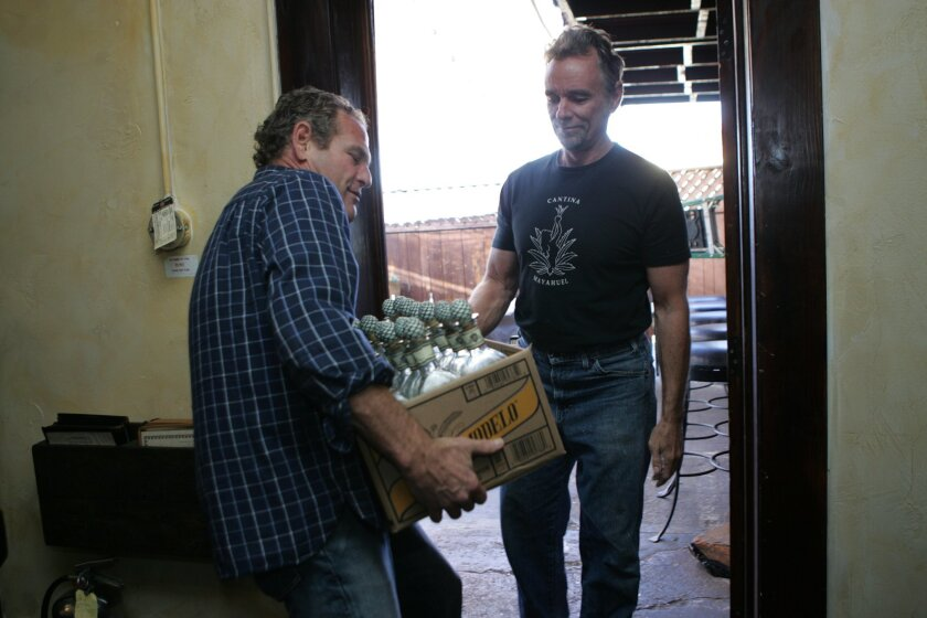 Steve Cherry (left), co-owner of Bottlehood, received empty handblown tequila bottles from Larry Auman, the owner of Cantina Mayahuel in North Park.