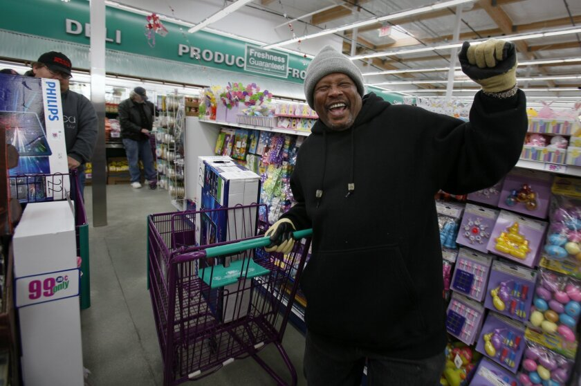 Vernell Gillard of Golden Hill celebrates being one of the nine people to be able to purchase a flat screen 22 TV for 99 cents Thursday morning at the opening of a new 99 Cents Only store on Market Street.