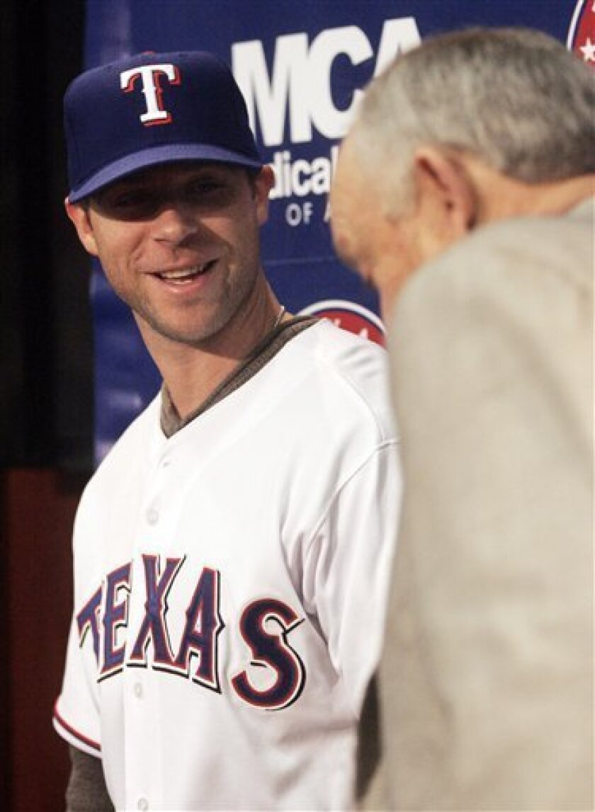 New Texas Rangers baseball player Rich Harden, left, talks with team president Nolan Ryan during a news conference in Arlington, Texas, on Friday, Dec. 11, 2009. (AP Photo/Mike Fuentes)