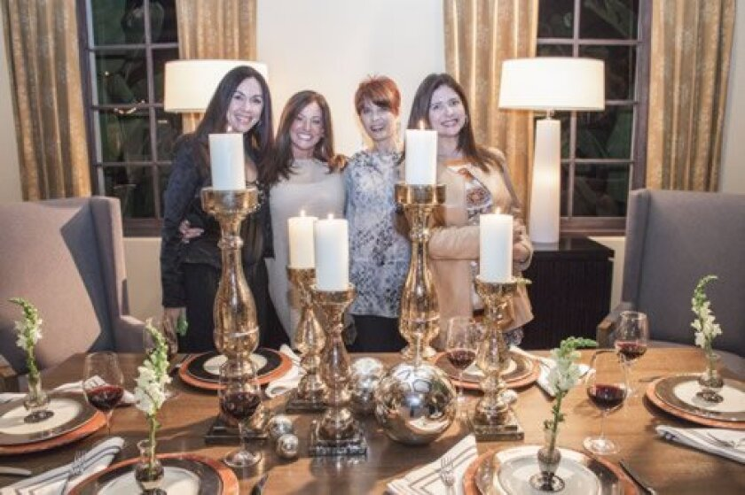 Admiring a candlelit table from Marso Collection are Dulce DeHaven, Liz Tapper, Suzie Helfrich and Renee Aranjo.