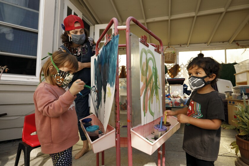 Kirsten Hove, left, works with two children doing watercolor paintings.