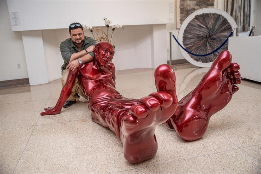 """Fotografía sin fecha cedida hoy, sábado 14 de abril de 2018, donde aparece el escultor franco-israelí Idan posando junto a una obra de su serie """"Bigfoot"""" (Pies grandes), expuesta en el Hotel Sagamore de Miami, Florida (EE.UU.). Zareski no sabía """"cuál era su casa"""" hasta que se convenció de que era donde """"tenía los pies"""", un sentimiento que plasma en """"Bigfoot"""", una serie de esculturas con pies gigantes que nos dicen que la tierra que pisamos todos """"es la misma"""". EFE/Gasen/SOLO USO EDITORIAL/NOVENTAS"""